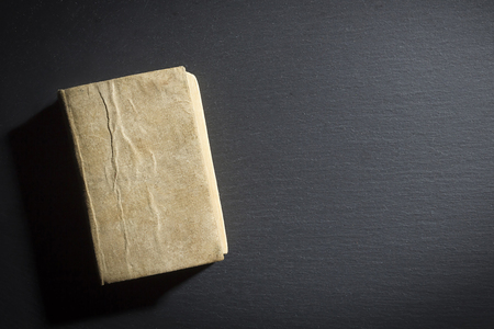 Closed old book on a black matte surface 版權商用圖片