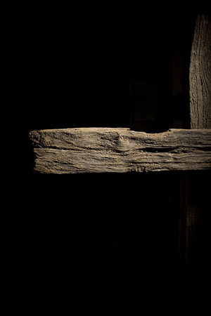 Old rotten logs stacked in crossbeams on a black background Stock Photo