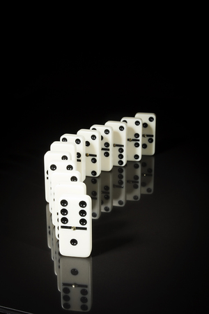 Stacks of Dominoes on a black reflective surface