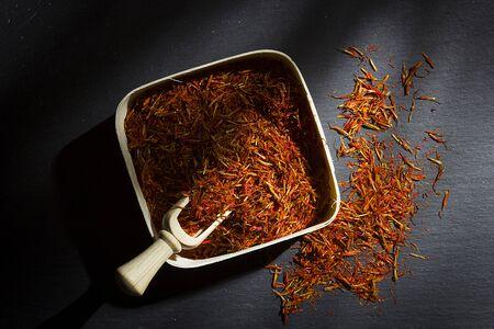 Saffron in a box on a black stone cutting board Standard-Bild