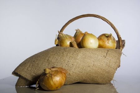 Ripe onions in a wicker basket on a white background 版權商用圖片