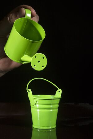 Green watering can and bucket on black background