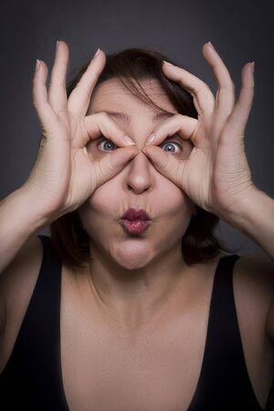 Frau verzieht das Gesicht vor der Kamera auf schwarzem Hintergrund