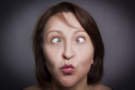 Woman grimaces in front of camera on black background