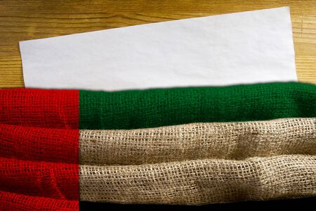 State flag United Arab Emirates of dense fabric with a sheet of aged paper for information.
