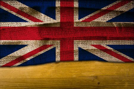 National flag United Kingdom of coarse fabric on a wooden surface Foto de archivo
