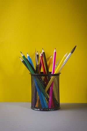 Multicolored pencils in a black stand on a yellow background
