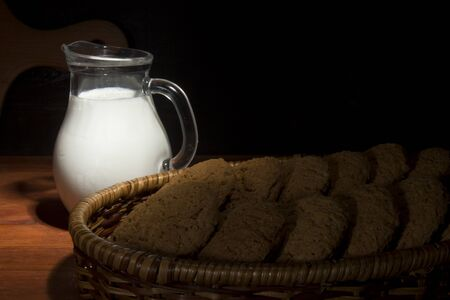 Jug with milk and pastries on the table Imagens