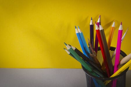 Multicolored pencils in a black stand on a yellow background Stock Photo - 129705149