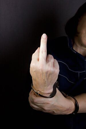 Female hands in handcuffs with a raised middle finger Stock Photo