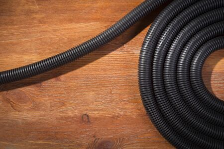 Corrugated hose for electrical wiring on a wooden table
