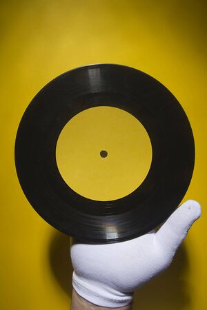 Hand in a white glove holding a vinyl record