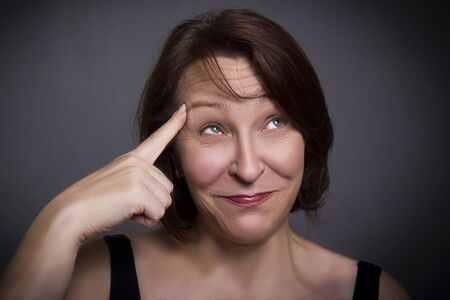 Woman grimaces in front of camera on gray background Stock fotó
