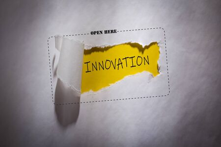 Torn paper with text innovation in the hole - open here Imagens