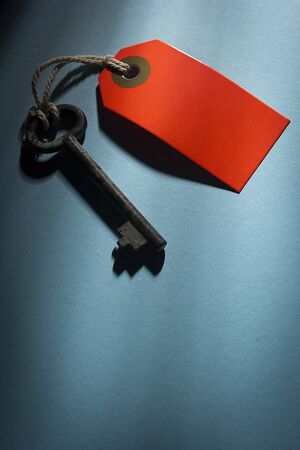 Old key with red tag on a blue table