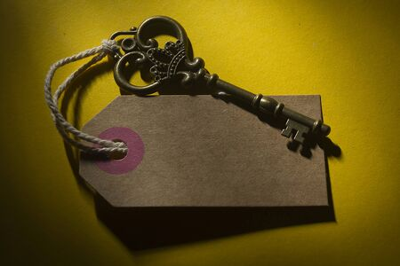Old key with a tag on a yellow background