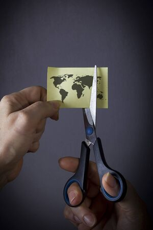Hand with scissors cuts the world map