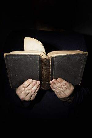 Female hands with an old book on a black background Stockfoto