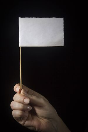 Female hand with a white flag on a black background