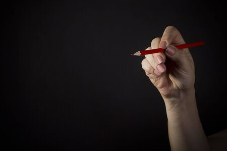 Female hand with a red pencil on a black background