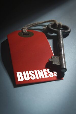 Red label with the word Business and old key.