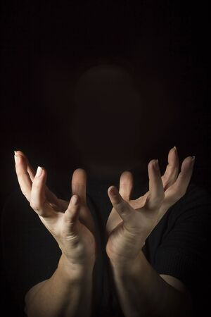 Outraged womans hands with spread fingers on a black background