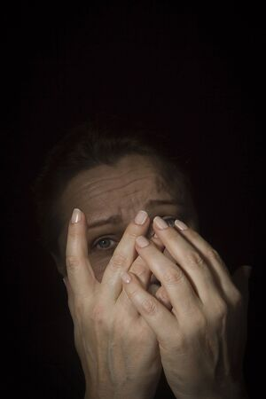 Elderly caucasian woman with hands covered her face feeling worried