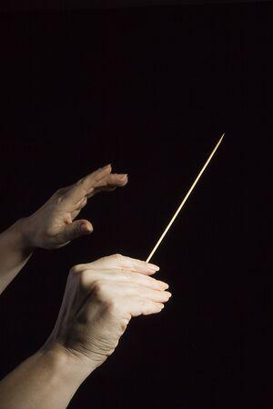 Mains féminines d'un chef d'orchestre sur fond noir