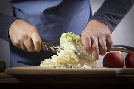Hands with a knife chopping cabbage on the kitchen table