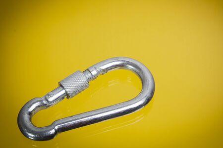 Aluminium-Kletterkarabiner auf gelbem Grund
