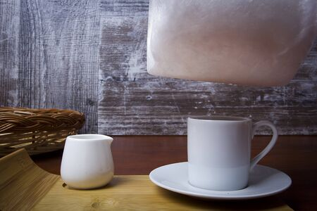 Cotton candy and cup of coffee on a wooden table Stockfoto