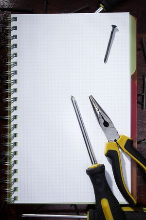 Screwdriver and pliers on a checkered notebook