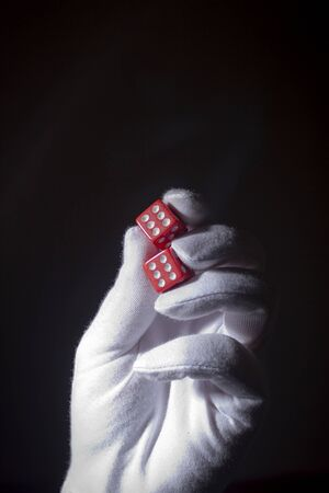 Hand in a white glove with red dice