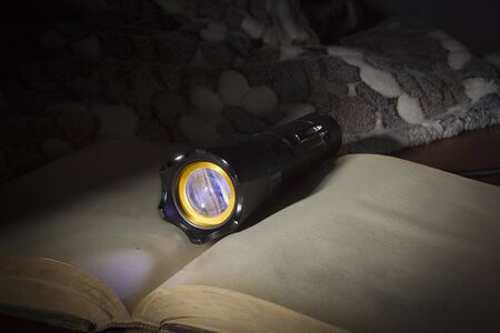 Black flashlight and old book on a wooden table