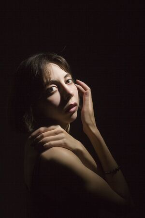 Portrait of a young beautiful woman on a dark background