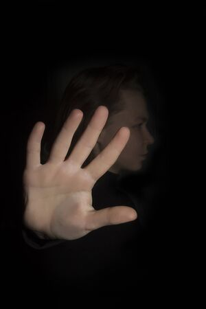 Young woman shows hand stop gesture on a black background Stockfoto