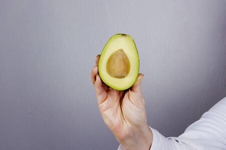 Hand in a white coat with avocado Stok Fotoğraf