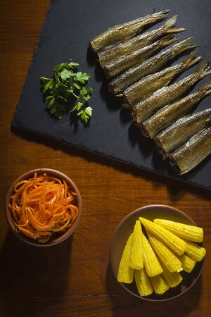 Smoked little fish on a black stone board