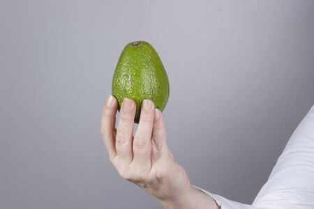 Hand in a white coat with avocado