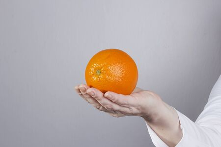 Hand in a white coat with an orange