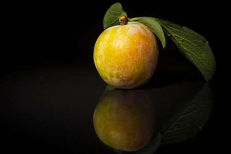 Ripe plums on a black reflective surface Reklamní fotografie