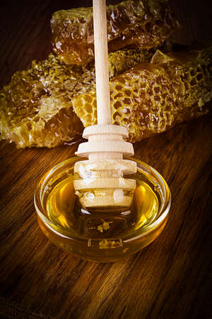 Yellow Honey and Honeycomb slice on a wooden table Imagens
