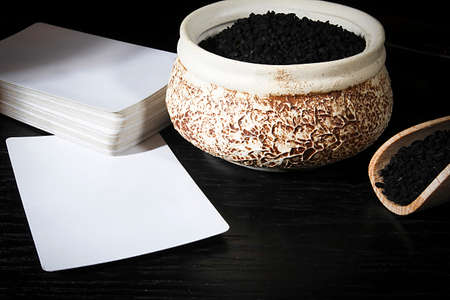 Black cumin seeds in pottery and white cards 版權商用圖片