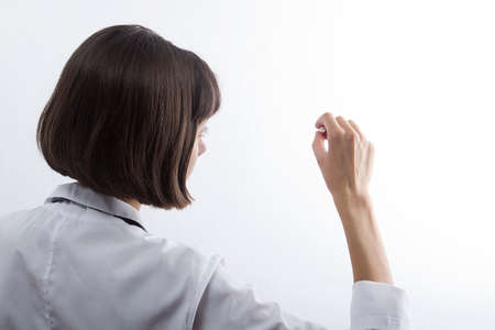 Female medical student with chalk in hand on white background 版權商用圖片