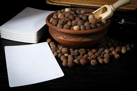 Allspice in pottery with wooden spoon and cards