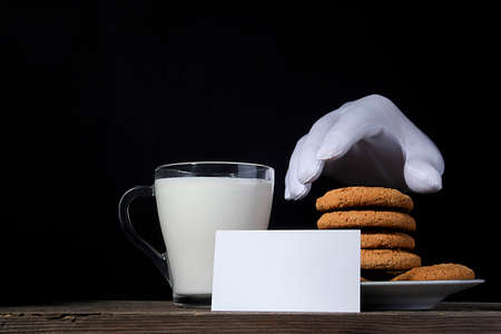 Cookies and milk for Santa on a black background