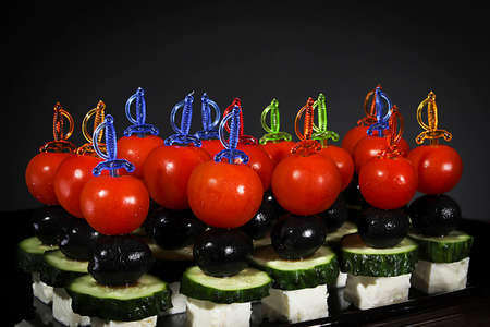 Many beautiful canapes on skewers on a gray background