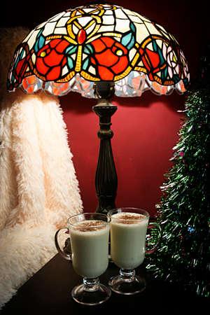 Christmas eggnog milkshake on table with christmas tree and table lamp