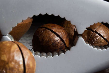 Macadamia nuts and nutcracker on wooden table