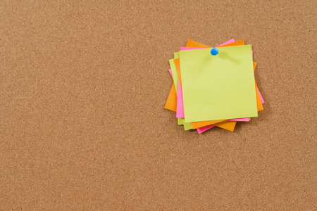 chit: Colorful post it notes on cork bulletin board.